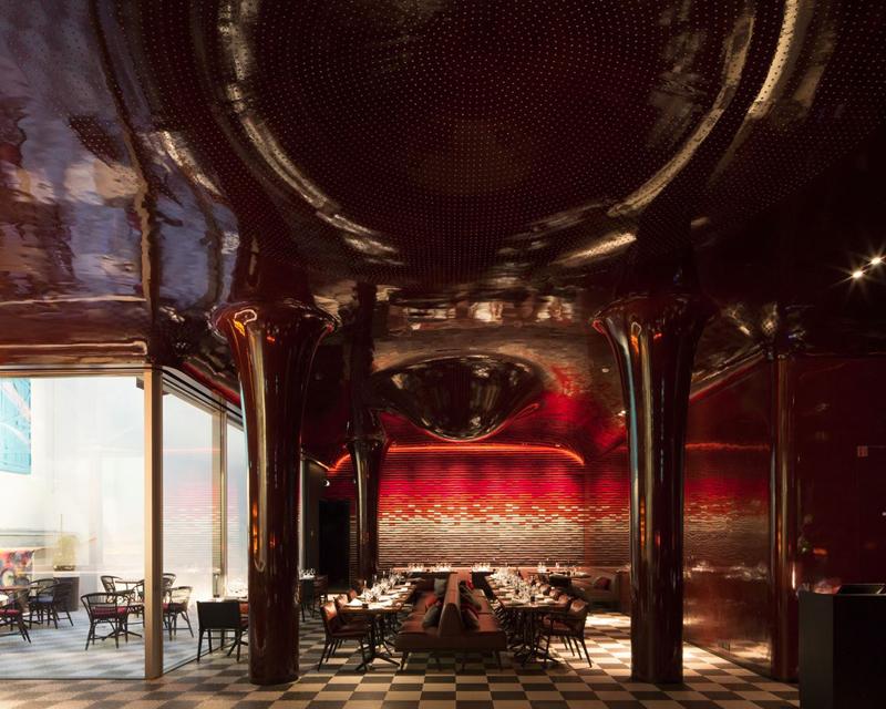 Restaurant à la décoration dans les tons rouges, plafond sculptural